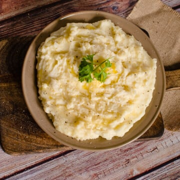 Flawless Mashed Potatoes- Easy Side Dish Recipe served in a brown bowl on a wooden chopping board with butter and parsley on top of the mash for garnish