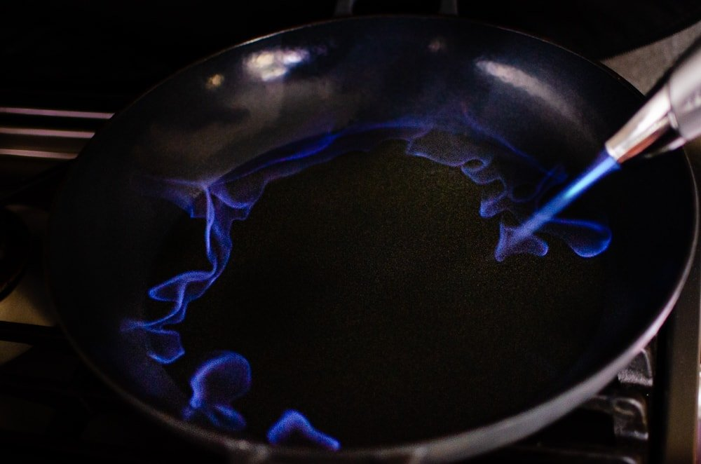 Setting the whisky alight with a kitchen blow torch in a cast iron pan