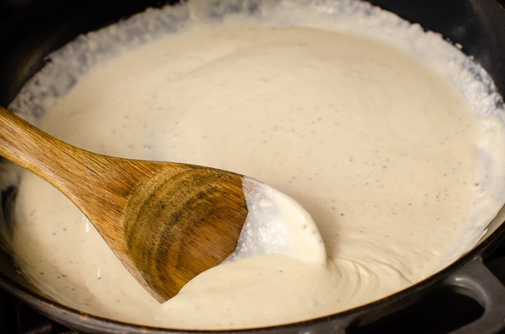 Stirring the creamy whisky sauce with a wooden spoon