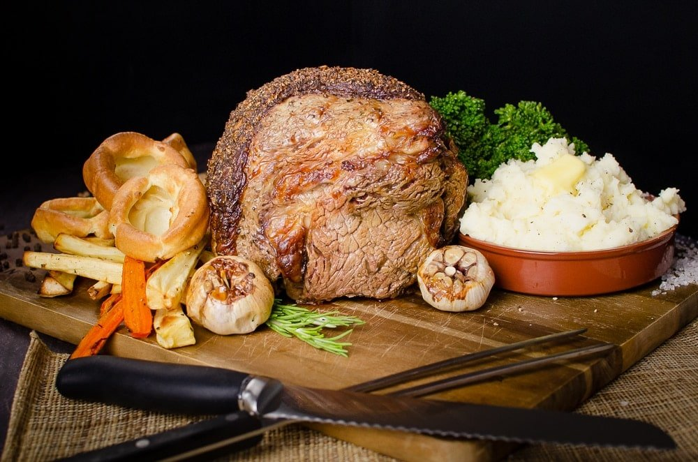 Rolled rib of beef boneless roast joint served on a wooden chopping board with flawless Yorkshire puddings, roasted parsnips, carrots, garlic bulbs,sprigs of rosemary, broccoli and creamy mash in a brown bowl