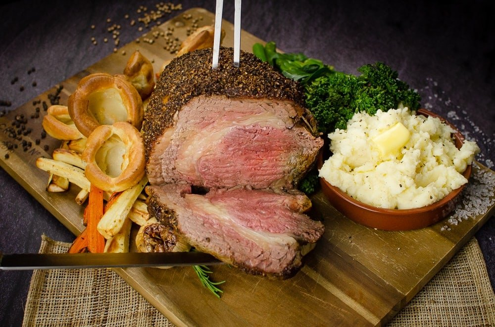 Cutting our Rolled rib of beef boneless roast joint into slices with a silver meat fork and silver knife on a wooden chopping board served with flawless Yorkshire puddings, roasted parsnips, carrots, garlic bulbs,sprigs of rosemary, broccoli and creamy mash in a brown bowl