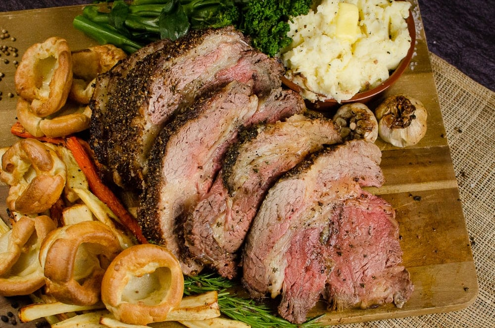Slices of Rolled rib of beef boneless roast joint on a wooden chopping board served with flawless Yorkshire puddings, roasted parsnips, carrots, garlic bulbs,sprigs of rosemary, broccoli and creamy mash in a brown bowl