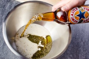 Newcastle Brown Ale being poured on top of the olive oil and mixed herbs in a silver bowl to make our beef marinade
