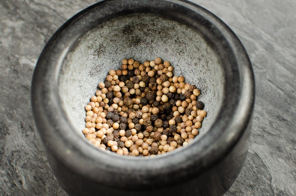 Peppercorns and coriander seeds in a black mortar ready to be crushed
