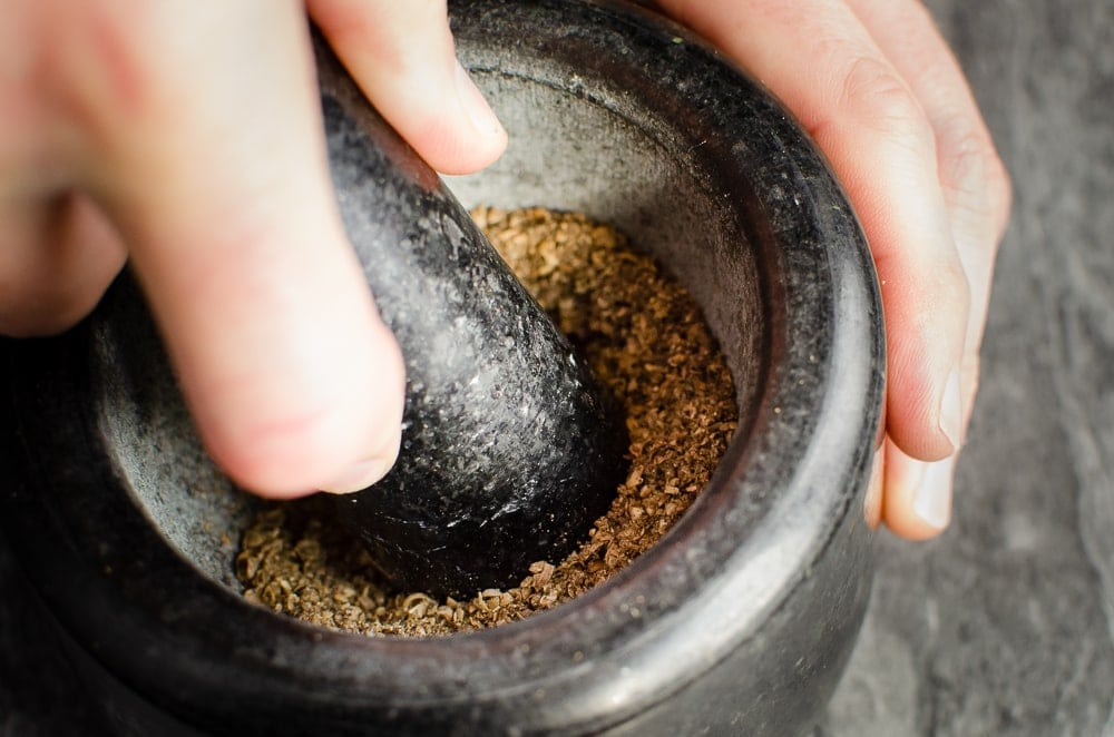 Crushing peppercorn and coriander seeds with a black pestle and mortar