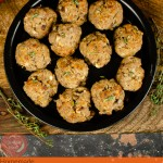 Image for Pinterest of our Sausage Meat Stuffing Balls with Apple and Chestnut served in a black metal dish, on a brown wooden chopping board with a red and green tartan cloth in the background