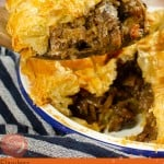 Image of our Steak Ale and Mushroom Pie for pinterest served in a white pie dish and being served up with a large wooden spoon