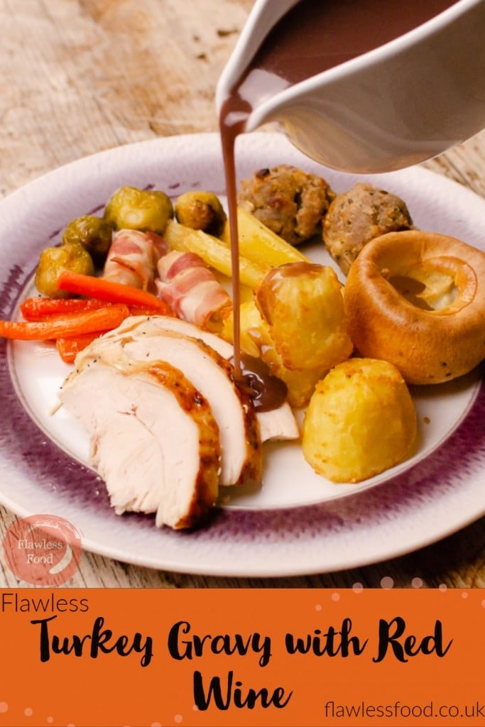 Image for pinterest of our Turkey Gravy with Red Wine in a white gravy boat being poured over a sliced turkey,roast potatoes, flawless Yorkshire puddings,pigs in blankets and glazed carrots, Brussel sprouts and parsnips served on a white and purple plate for Christmas dinner