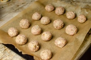 Sausage Meat Stuffing Balls with Apple and Chestnut made from scratch on a baking tray lined with brown parchment paper