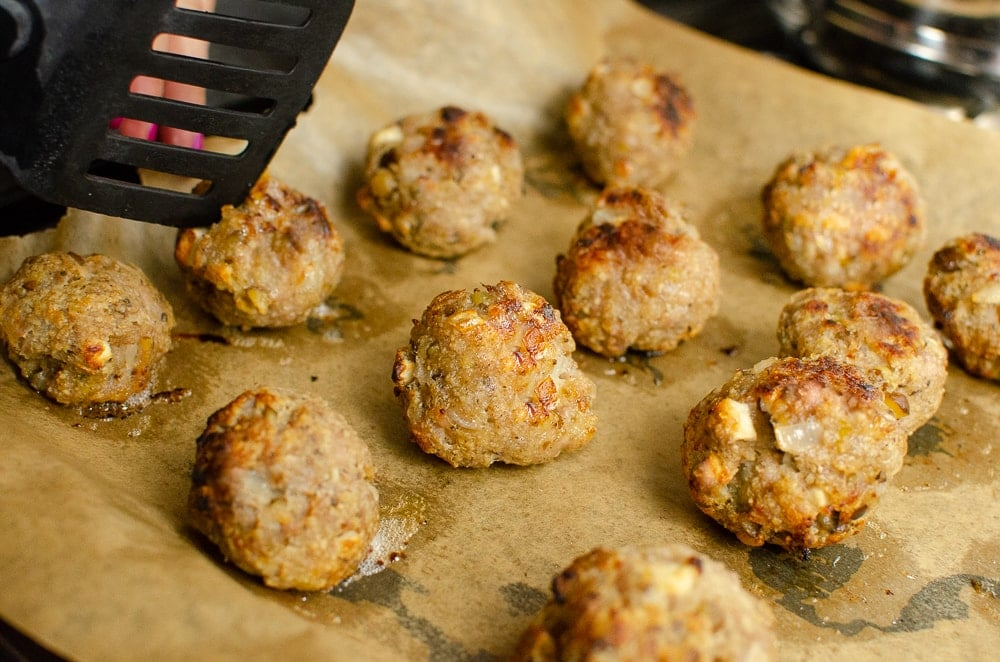 Easy Homemade Cooked Sausage Meat Stuffing Balls with Apple and Chestnut on baking tray lined with brown parchment paper