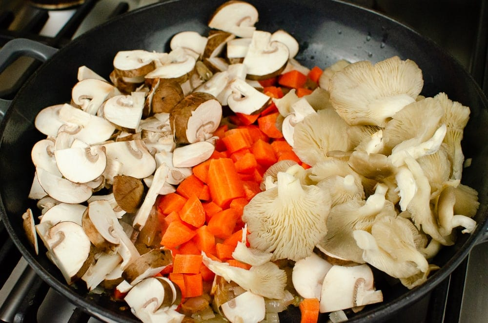 Chopped onion, carrots, chestnut and oyster mushrooms cooking in a cast iron pan