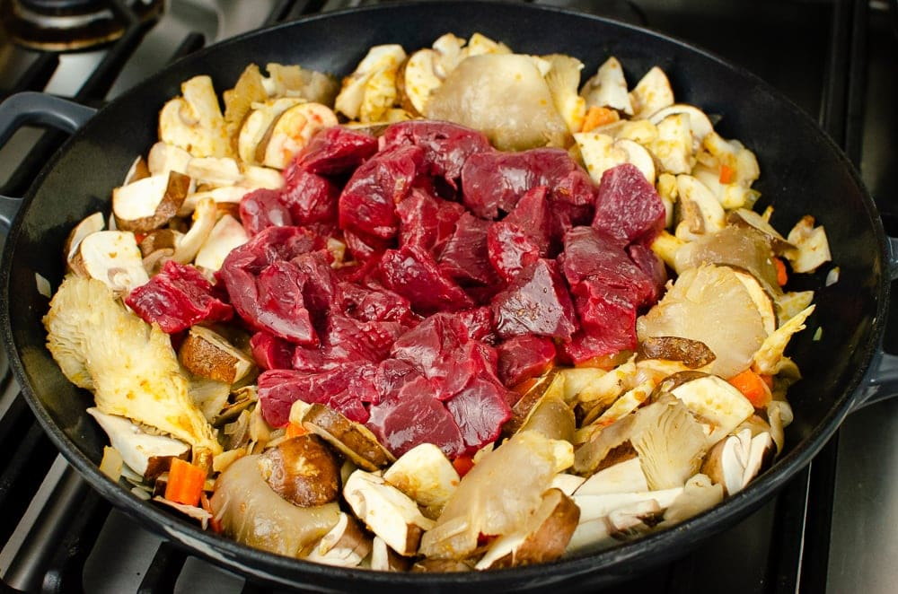 Diced beef, chopped onion, carrots, chestnut and oyster mushrooms cooking in a cast iron pan