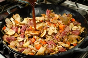 Pouring in beef stock into a cast iron pan cooking Diced beef, chopped onion, carrots, chestnut and oyster mushrooms in a cast iron pan