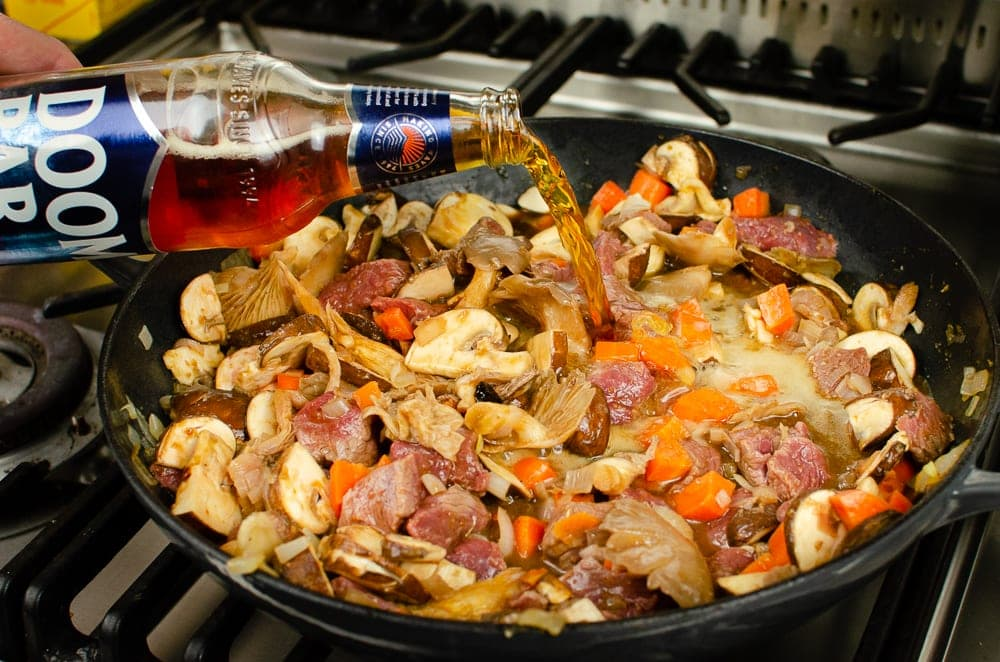 Pouring Doombar ale into the steak and ale filling cooking in a cast iron pan