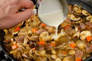Pouring pain flour mixed with water into the steak and ale filling cooking in a cast iron pan
