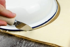 Cutting a circle shape with a silver knife using a white and blue pie dish to shape