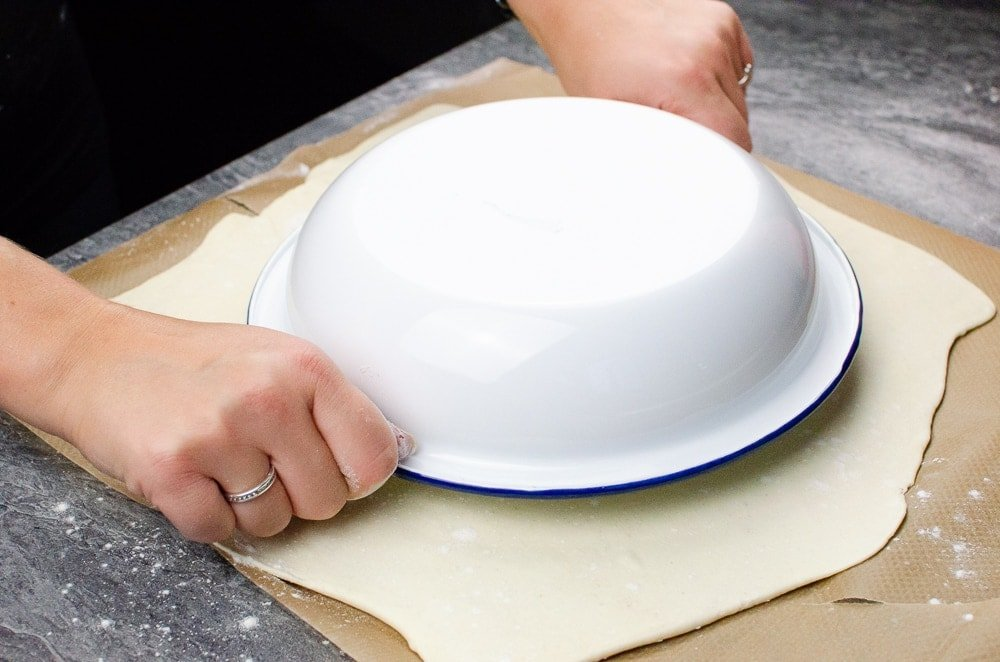 Placing the white and blue pie dish on top of the puff pastry to make the circle shape for the pie