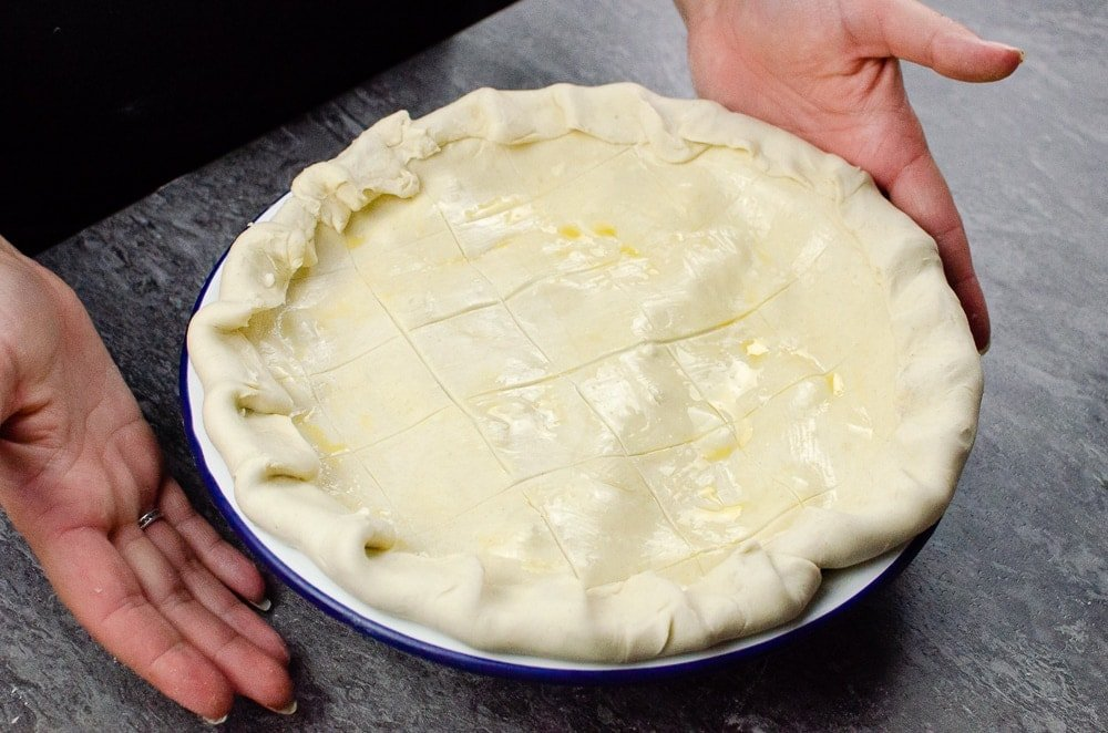 Steak Ale and Mushroom Pie in a white and blue pie dish ready to go in the oven