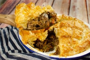 Taking out a slice of steak Ale and Mushroom pie with a wooden spoon