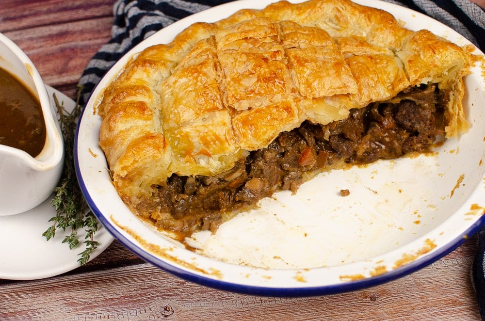 Steak Ale and Mushroom Pie cut in half in a white and blue pish and onion gravy in a white gravy boat served on the side