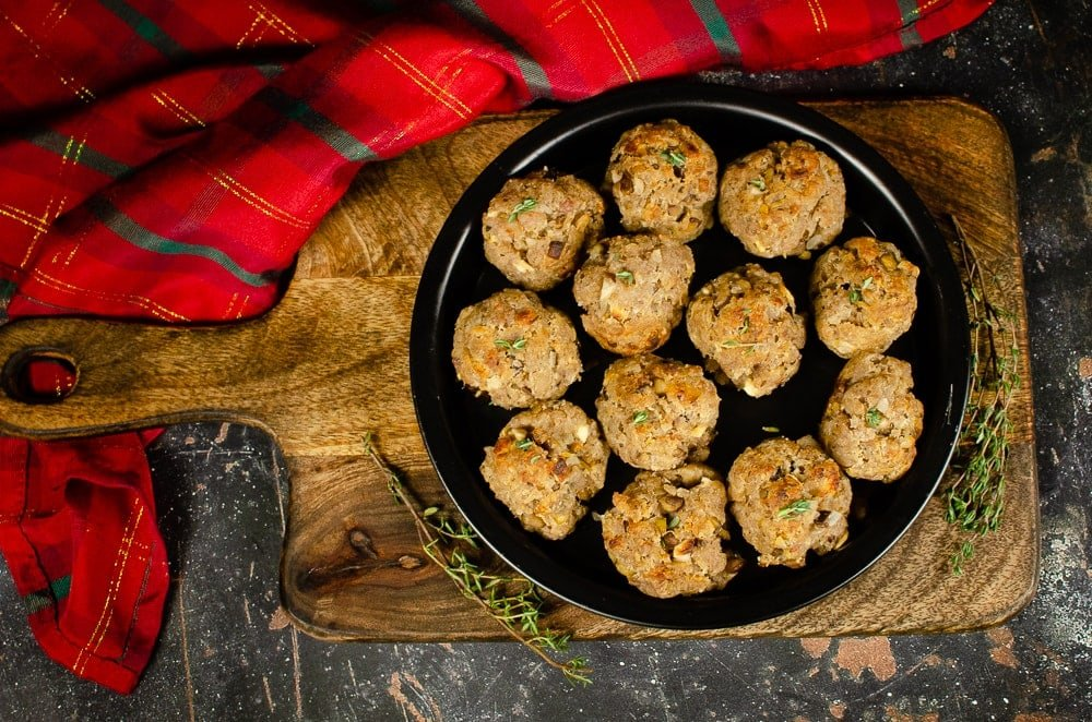 Sausage Meat Stuffing Balls with Apple and Chestnut with sprinkled thyme on top served on a black metal dish on a brown wooden chopping board with a red and green tartan cloth in the background