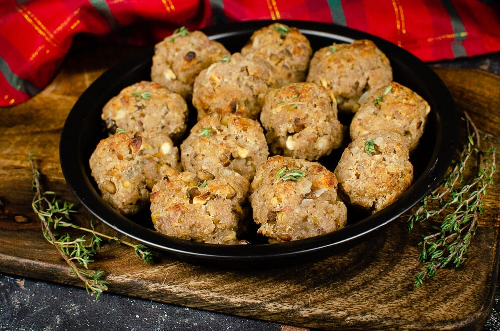 Close up picture of our Sausage Meat Stuffing Balls with Apple and Chestnut with sprinkled thyme on top served on a black metal dish on a brown wooden chopping board with a red and green tartan cloth in the background