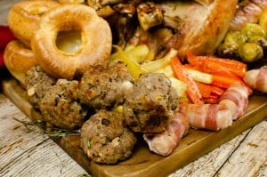 Sausage Meat Stuffing Balls with Apple and Chestnut served with all the Christmas trimmings like Cooked small whole turkey,pigs in blankets, Flawless Yorkshire Puddings, glazed parsnips,carrots and Brussel sprouts on a brown chopping board