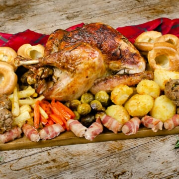 Our cooked Small Whole Turkey served on a brown wooden chopping board with red and green tartan sheet and all the trimmings like Flawless Yorkshire puddings,Flawless Roast potatoes,pigs in blankets, stuffing balls and maple glazed carrots,parsnips and Brussel sprouts