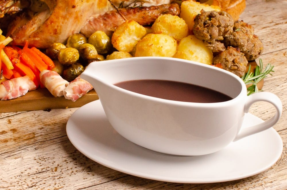 Turkey Gravy with Red Wine in a white gravy boat and saucer served next to stuffing balls,flawless roast potatoes, glazed carrots, Brussel sprouts,pigs in blankets and a roast turkey on a wooden chopping board