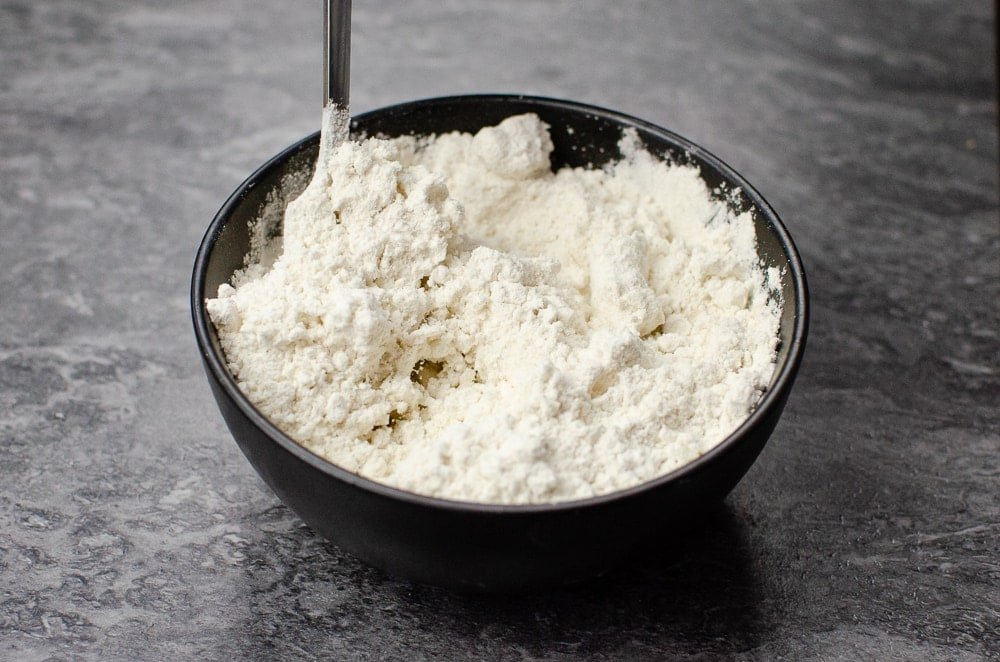 Plain white flour in a black bowl being stirred with a silver fork
