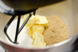 Brown sugar, butter and caster sugar in a silver cake mixer bowl