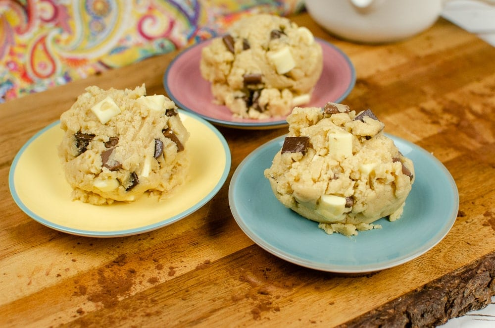 Edible Cookie Dough balls with chunks of white and milk chocolate chunks served on pink,yellow and blue dishes on a wooden board sprinkled in cocoa powder