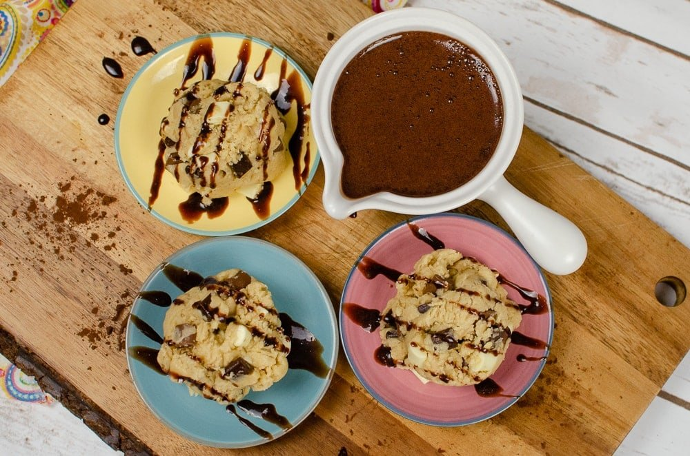 Edible Cookie Dough with drizzled chocolate sauce on top served out on three dishes, one pink , one blue and one yellow all served on a brown wooden board with homemade chocolate sauce on the side in a white small sauce pot