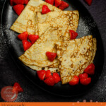 Pin image of our Easy English Pancakes served on a black plate with strawberries