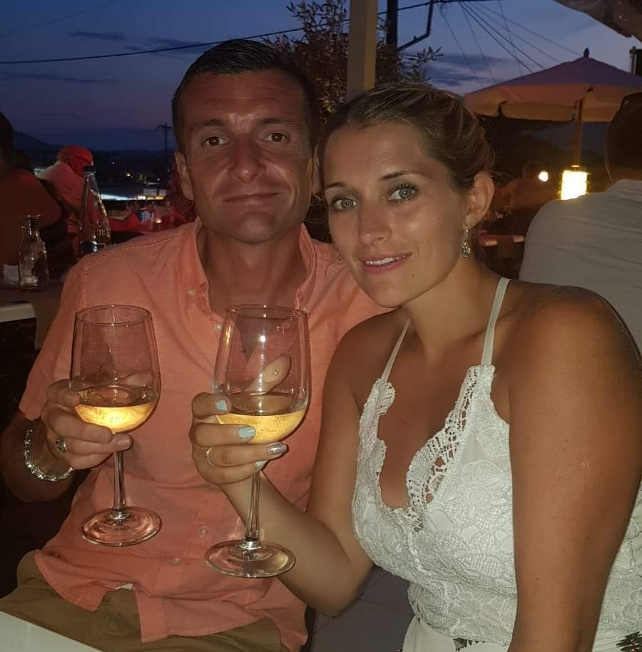 Luke and kay holding glasses of wine whilst on holiday in Greece