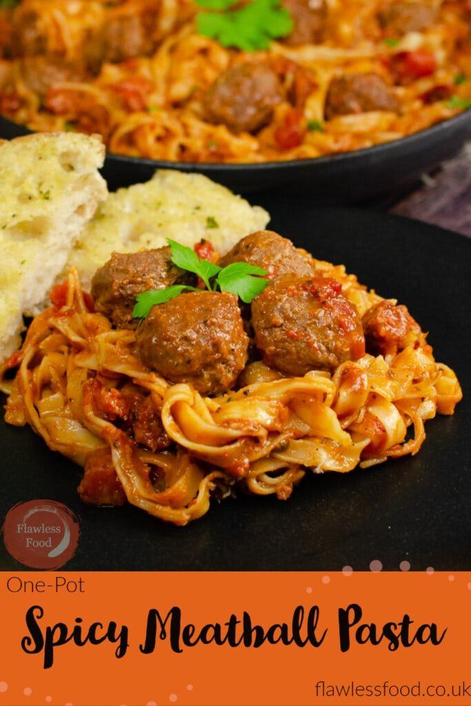 Pinterest image of our One-Pot Spicy Meatball Pasta served on a black plate with garlic bread on the side