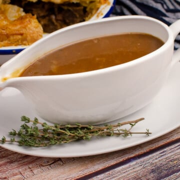 Easy Onion Gravy with Ale in a white gravy boat with a steak and ale pie in the background