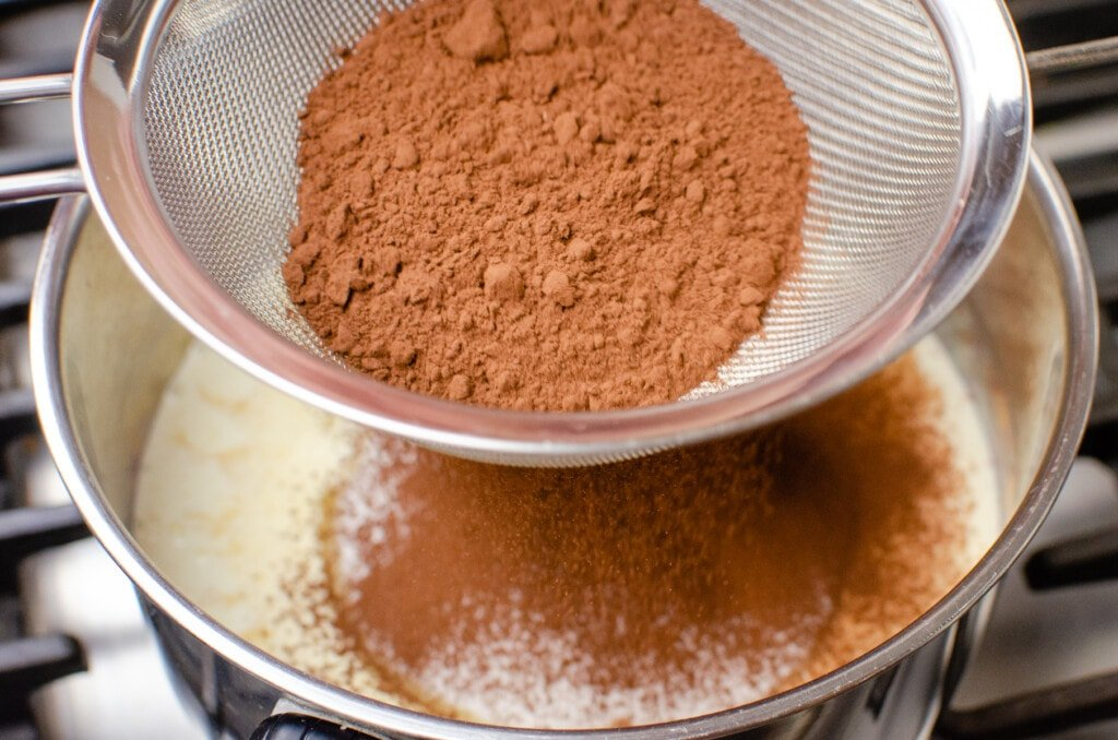 Sieving cocoa powder into the cream mixture in a silver saucepan