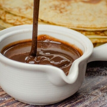 pouring our easy chocolate sauce into a white pouring jug served with a stack of English pancakes in the background