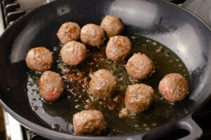 Beef meatballs cooking in olive oil in a grey cast iron pan