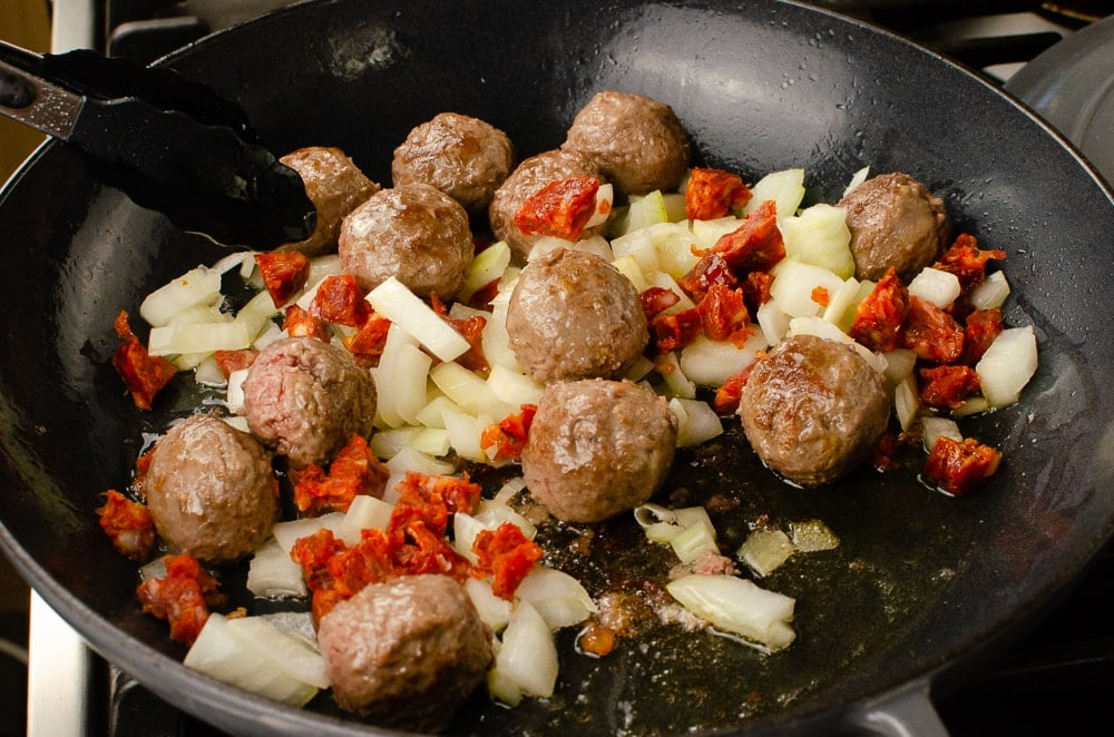 Meatballs, chopped onions and chopped chorizo cooking in olive oil in a grey cast iron pan