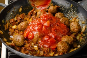 Pouring a can of chopped tomatoes over the Spicy Meatballs cooking in a grey cast iron dish