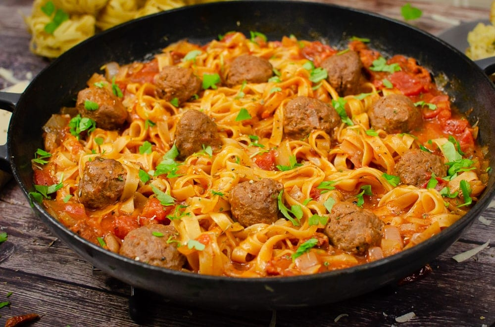 One-Pot Spicy Meatball Pasta served in a cast iron pan with sprinkled chopped parsley on top for garnish