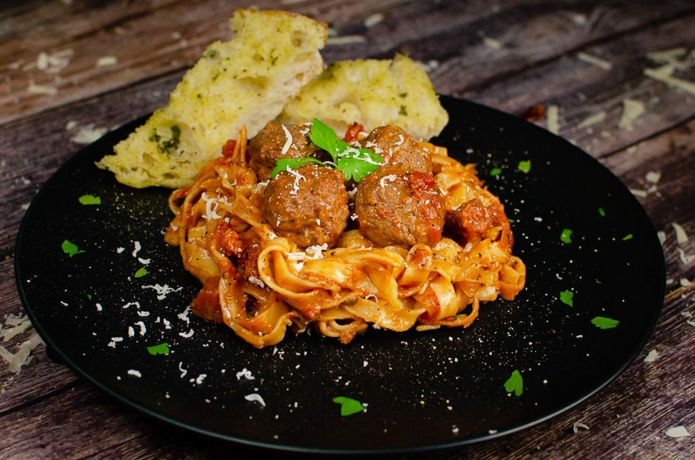 Spicy Meatball Pasta served on a black plate with garlic bread on the side with a garnish of chopped parsley and grated parmesan over the top of the food
