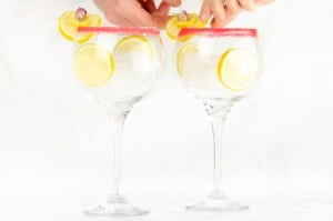 Two sugar rim gin glasses with ice cubes and slices of lemons inside the glasses and placing lemon garnish with a rose petal onto the glass rim by hand