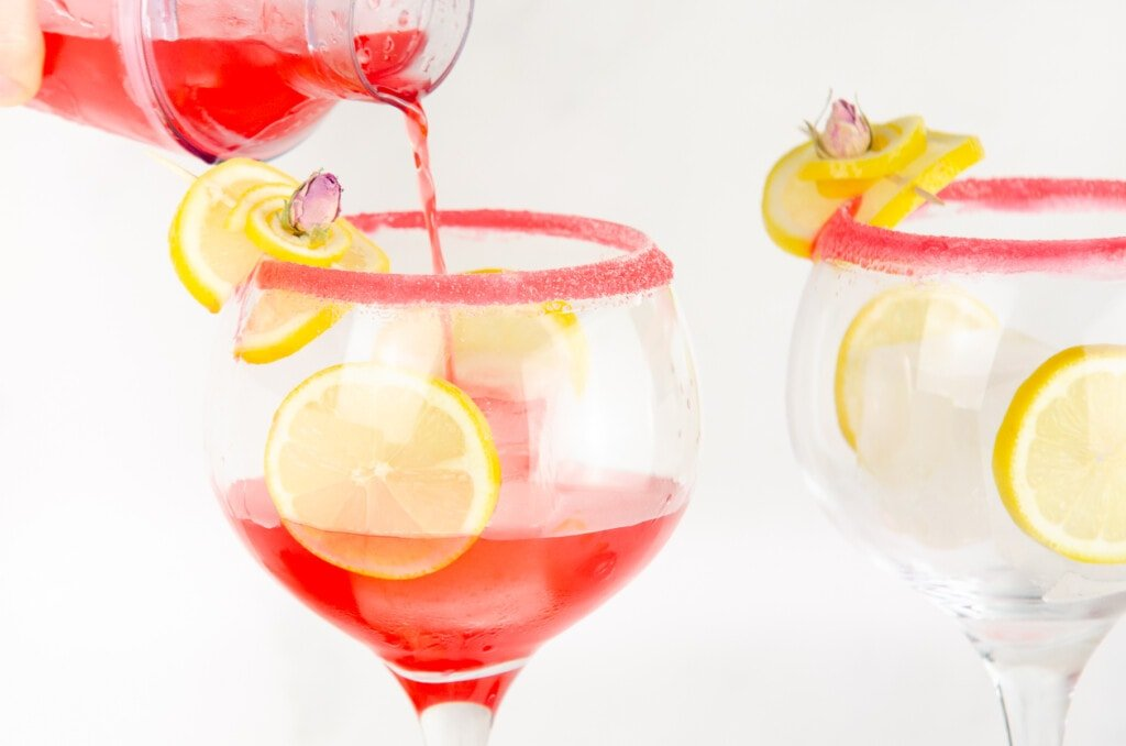 Pouring gin fizz into a large gin glass sugar rimmed garnished with lemon slice and rose petal with slices of lemon and ice cubes in the glass