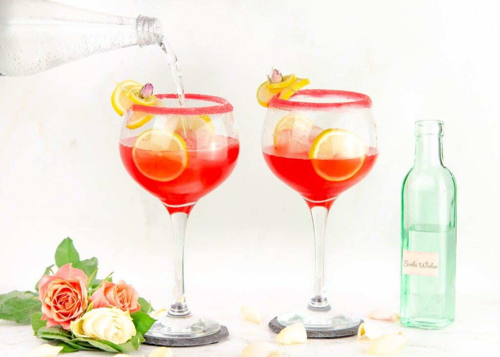 Pouring soda water into sugar rim glasses garnished with lemon slices and cubes of ice in the glass and pink and white roses at the bottom of glass and green bottle of soda water in the background
