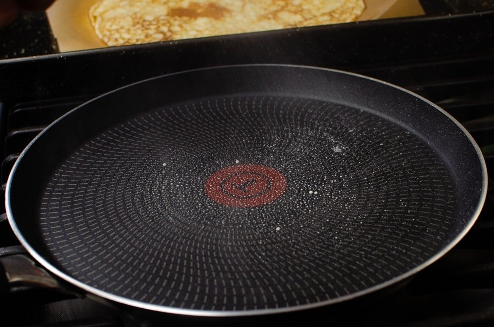 Spraying oil onto a pancake frying pan to cook our Easy English Pancakes