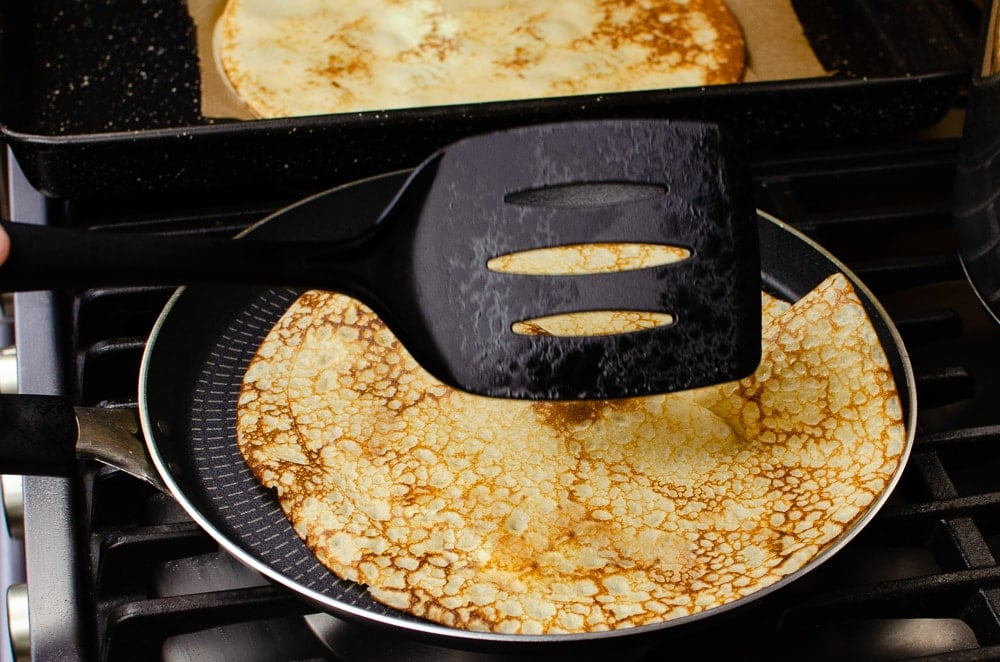 Turning our homemade British pancake over with a black spatula