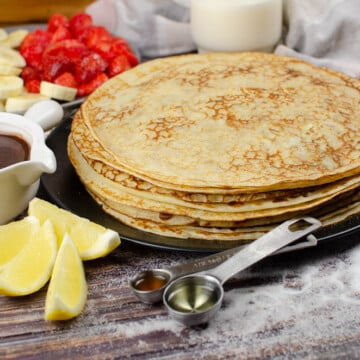 A stack of Easy English Pancakes on a black plate on a surface of scattered sugar with a white pot of chocolate sauce, plate of chopped strawberries and bananas, a glass of milk, two eggs, slices of lemon,½ tablespoon of vegetable oil and ½ teaspoon of vanilla extract on the side